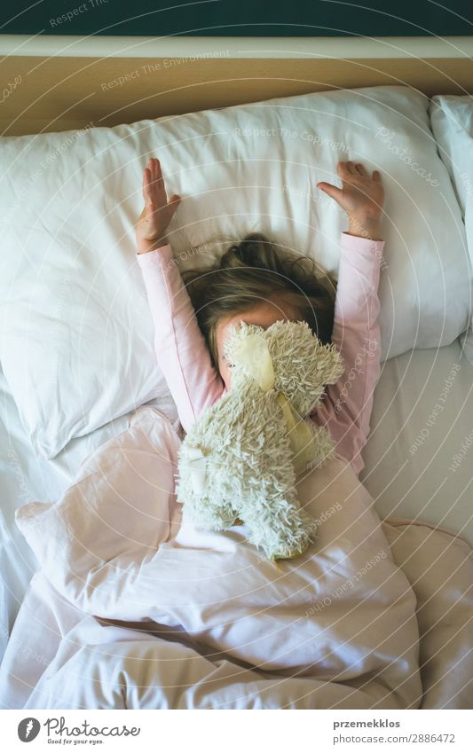 Little girl lying in a bed with teddy bear at the morning. Happy mornings. Girl child enjoying morning in bed Beautiful Playing Child Human being Woman Adults