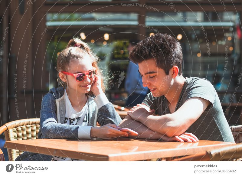 Young people sitting in cafe talking and using mobile phones Lifestyle Joy Happy Summer Table Restaurant Telephone PDA Technology Boy (child) Woman Adults Man