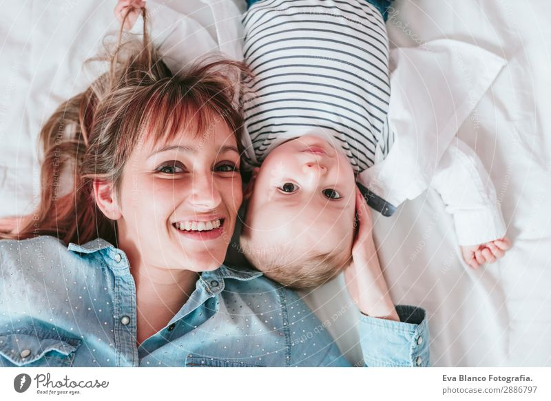 happy young mother and her baby boy lying on bed and smiling Woman Child Human being Youth (Young adults) Young woman Blue Joy Lifestyle Adults Love Feminine