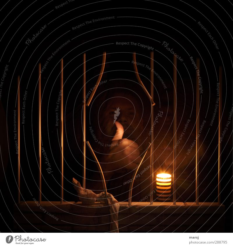 Freedom! Free at last! Human being Masculine Man Adults Face Hand Thumb Fist 1 30 - 45 years Window Candle Flame Concrete Steel jail lattice bars Illuminate