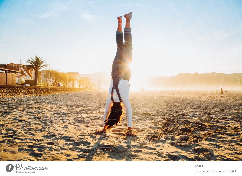 Little girl standing on hands on the beach at sunset Joy Happy Beautiful Playing Vacation & Travel Freedom Summer Beach Ocean Child Nature Sand Sky Coast Jeans
