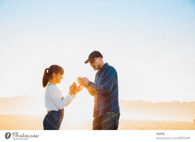 Father and daughter playing hands game on the beach at sunset Joy Happy Beautiful Playing Sun Beach Child Adults Family & Relations Jeans Bald or shaved head