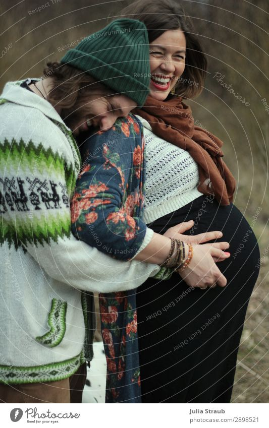 Heavily pregnant woman laughs and rejoices with her husband Parents Adults Couple Partner 2 Human being 30 - 45 years Scarf Cap Brunette Long-haired Beard Touch