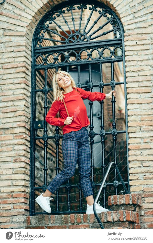 Happy young blond woman next to urban door. Woman Human being Youth (Young adults) Young woman Beautiful White Red 18 - 30 years Street Lifestyle Adults Autumn