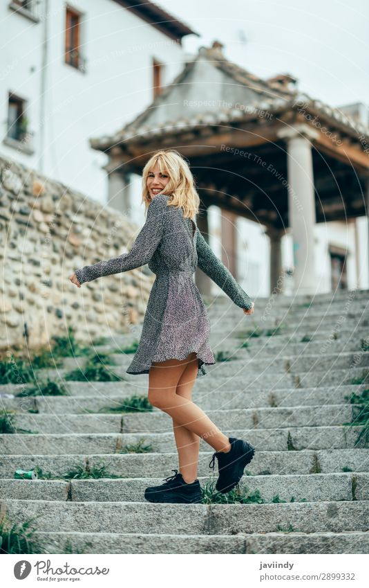 Smiling blonde girl wearing dress dancing outdoors. Woman Human being Youth (Young adults) Young woman Beautiful White Joy 18 - 30 years Street Lifestyle Adults