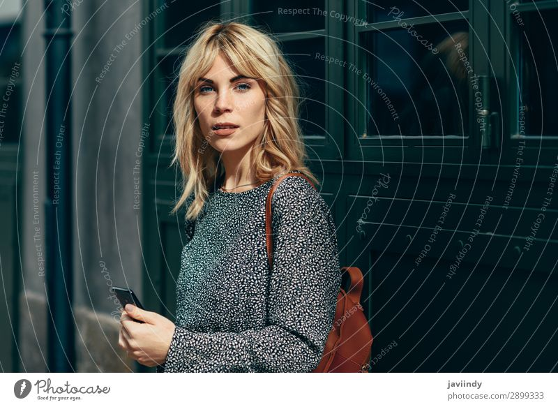 Attractive young caucasian woman looking at her smart phone in urban background Lifestyle Style Beautiful Hair and hairstyles Telephone PDA Human being Woman