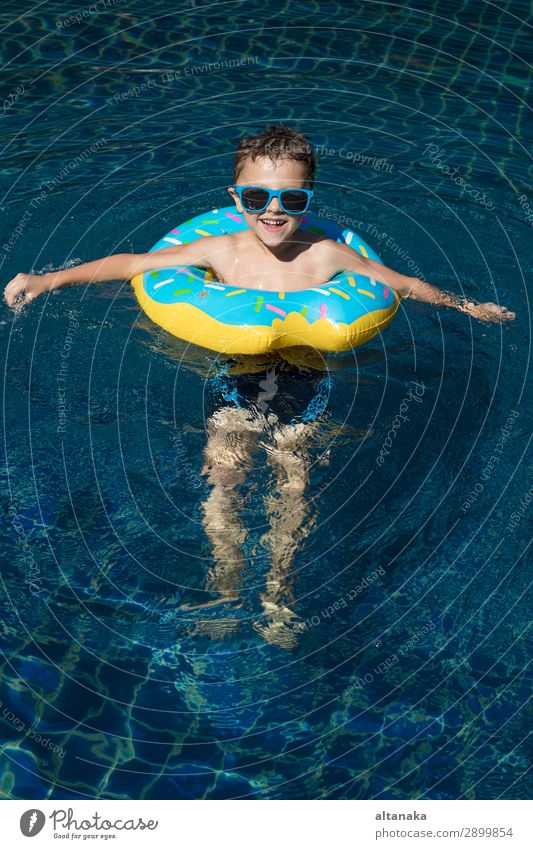 One little happy boy playing on the inflatable circle in swimming pool at the day time. Concept of friendly family. Lifestyle Joy Happy Face Relaxation
