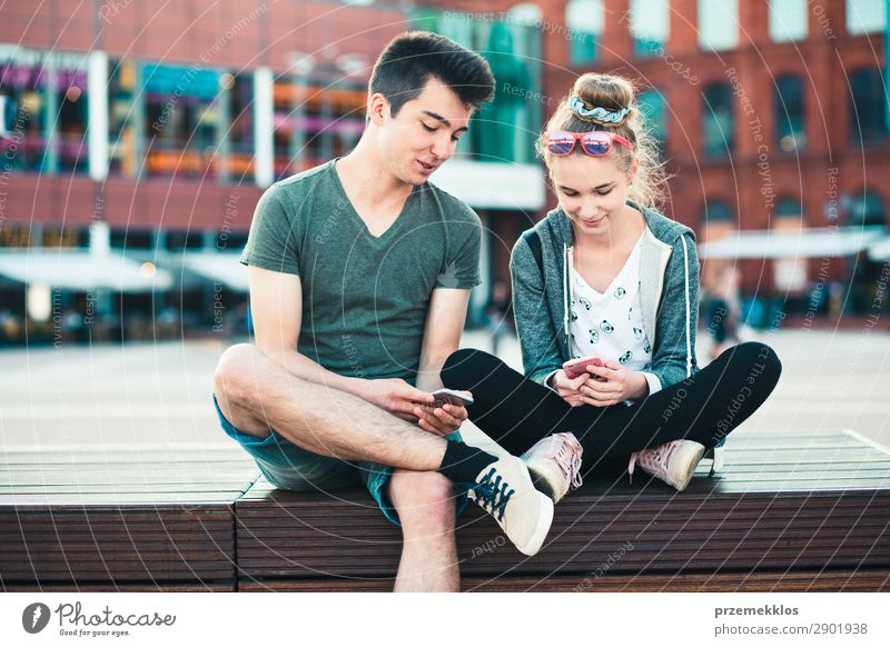 Couple of friends having fun together with smartphones Woman Man Summer Town Street Lifestyle Adults To talk Together Friendship Modern Technology Sit To enjoy