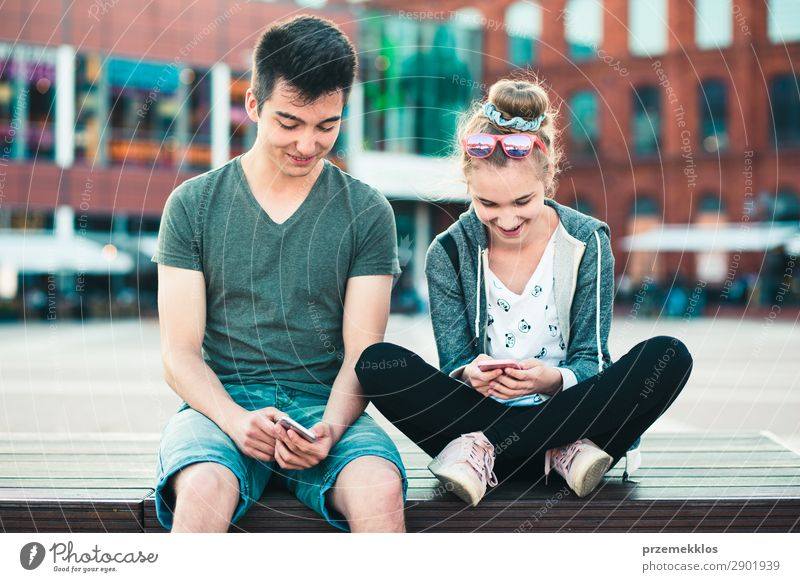 Teenage girl and boy, having fun together with smartphones Woman Man Summer Town Street Lifestyle Adults To talk Couple Together Friendship Modern Technology