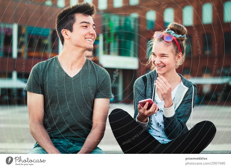 Couple of friends, teenage girl and boy, having fun together with smartphones, sitting in center of town, spending time together Lifestyle Summer To talk