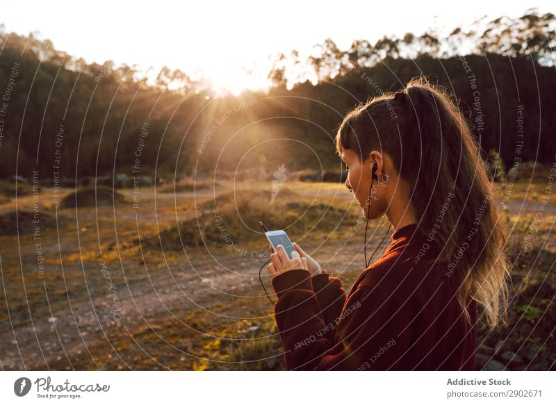 Young woman with piercing listening music on smartphone on hill Hipster Headphones PDA Music Listening Piercing Hill Landscape Street Youth (Young adults)