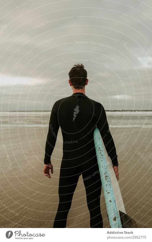 Person with surfboard standing near sea Human being Stand Surfboard Ocean Sand Wet Clouds Sky Lanzarote Spain Vacation & Travel Trip Leisure and hobbies