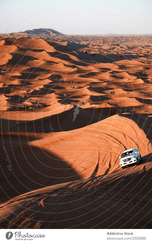 Automobile driving between hills in desert Car Desert Safari Dune off-roader Sand Dubai United Arab Emirates Driving Hill Beautiful weather Adventure