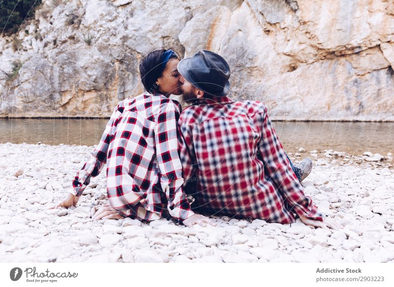 Positive woman and man resting and kissing on stone shore near river Couple Mountain River Stone Rock Smiling Woman
