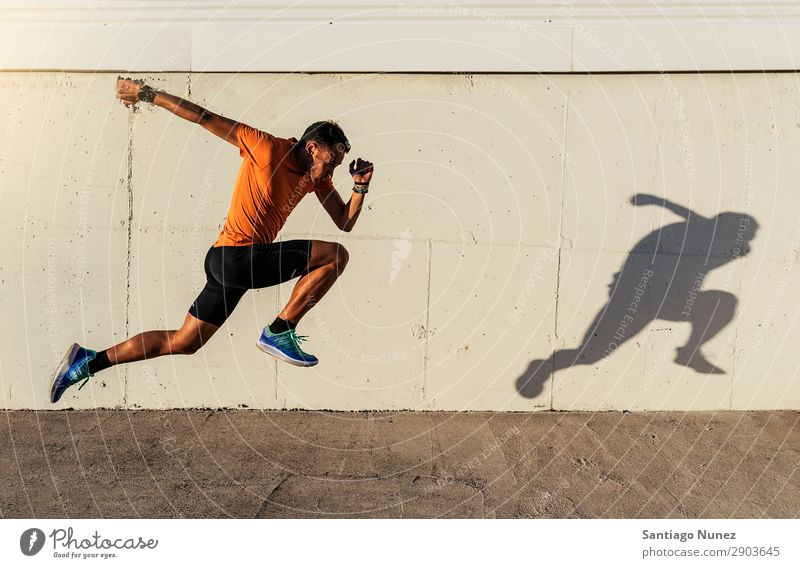 Handsome man running in the city. Man Running Jogging Runner Street City Athlete Speed Fitness Lifestyle Youth (Young adults) Town Action Shadow Healthy Sports
