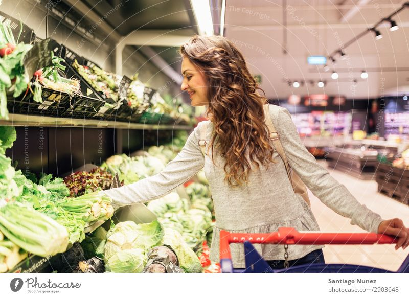 Beautiful woman taking a lettuce in supermarket. Woman Shopping Youth (Young adults) Supermarket Food Markets using Human being Smiling Cart pretty Lifestyle