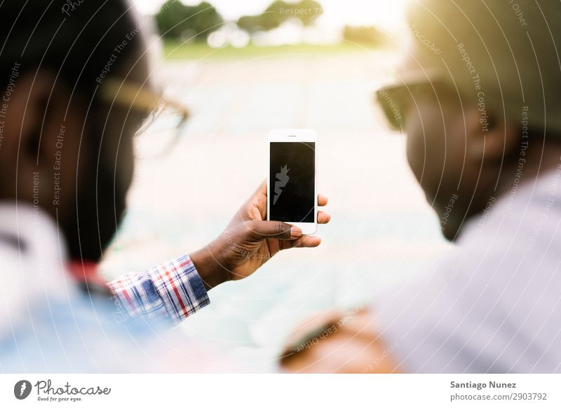 Two black race friends having fun with mobile. Friendship Telephone Cellphone Town African Black American Mobile Youth (Young adults) Man PDA Technology