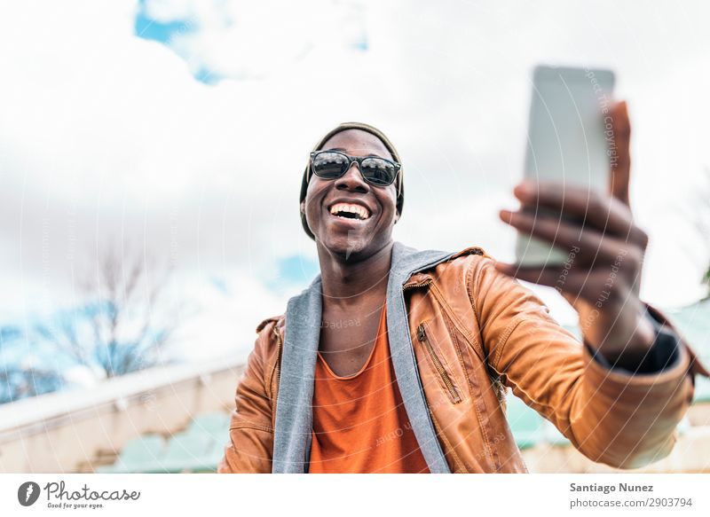 American man using mobile in the street. Man Telephone Cellphone Town African Black Mobile Youth (Young adults) Laughter PDA Technology Human being Happy