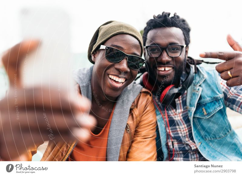 Two black race friends having fun. Friendship Telephone Cellphone Town African Black American Mobile Youth (Young adults) Man Laughter PDA Technology