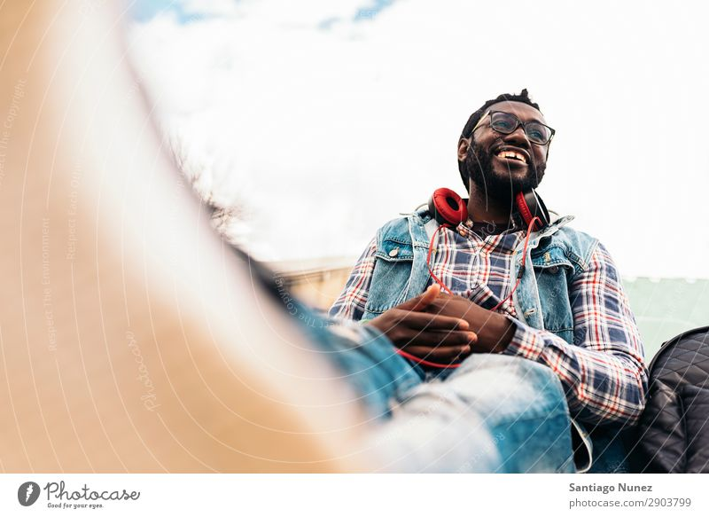 African Young Man Listening Music. Headphones Lifestyle Black American Town Portrait photograph Telephone PDA Mobile Solar cell handsome Technology Stand