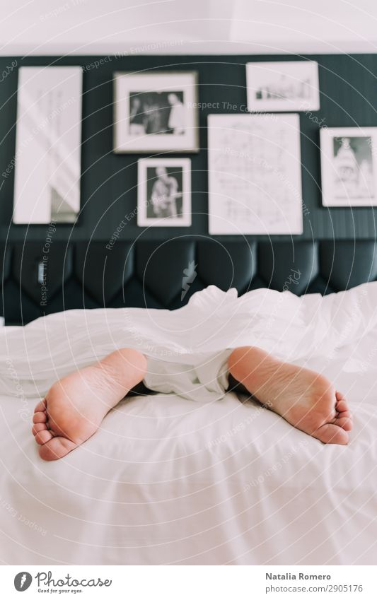 A bed with two feet coming out of the sheets Lifestyle Happy Skin Relaxation Vacation & Travel Bedroom Human being Adults Hand Fingers Feet Love Sleep White