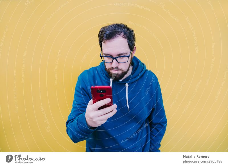 A young boy is looking at something on his mobile phone Lifestyle Happy Beautiful Music Telephone PDA Screen Camera Technology Human being Boy (child) Man