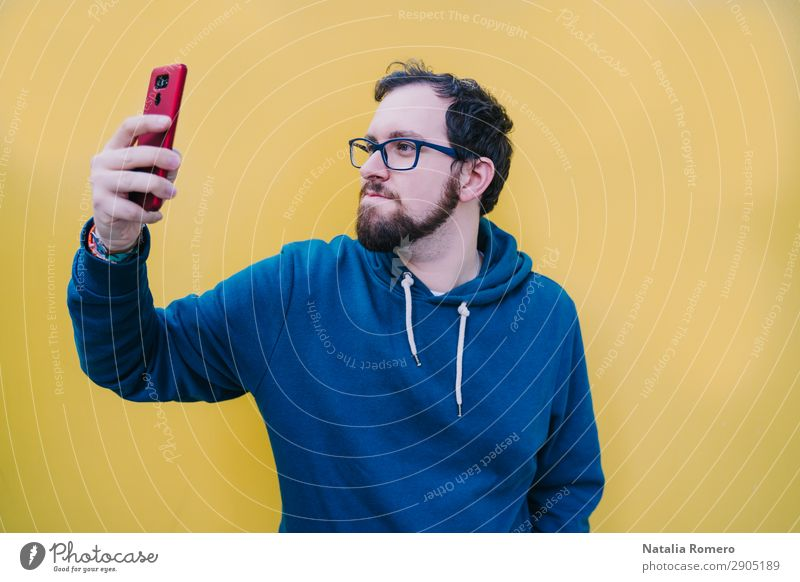 A young boy raises his arm to see something on the phone Lifestyle Happy Beautiful Music Telephone PDA Screen Camera Technology Human being Man Adults