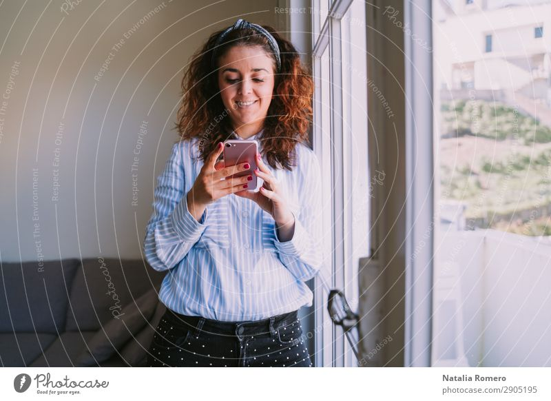 Young woman leans on the window looking at the mobile Happy Profession Workplace Office Business Company Telephone Cellphone PDA Human being Woman Adults