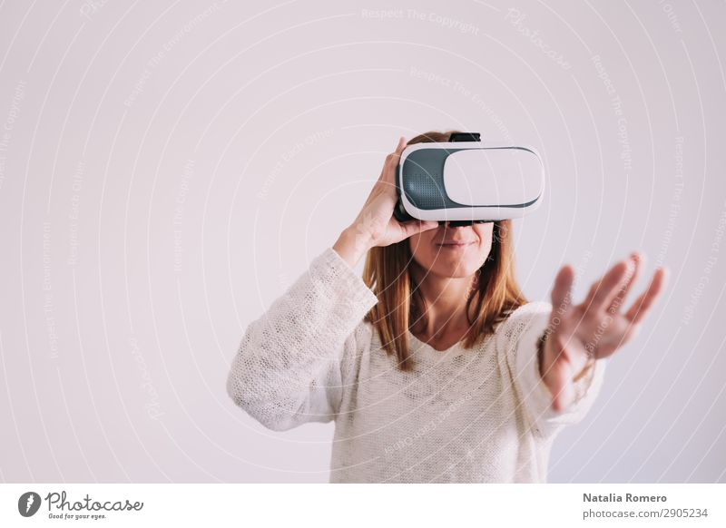 Young woman uses a virtual reality glasses Design Beautiful Playing Entertainment Technology Woman Adults Arm Hand T-shirt Modern New White Idea Virtual Video