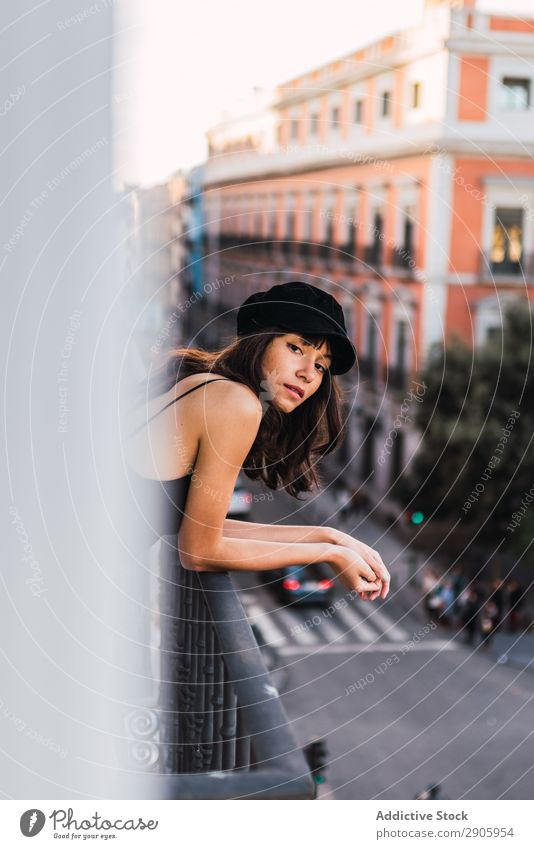 Attractive woman in cap on balcony in evening Woman Balcony Cap Street City Youth (Young adults) Home Evening Thin Building Charming Town