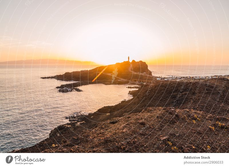 Lighthouse on stone shore near water at sunset Ocean Coast Street Sunset Tenerife Canaries Spain Water Beacon Evening Stone Vantage point Rock Amazing