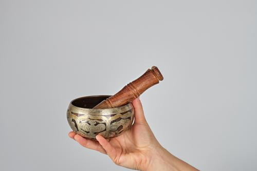 copper singing bowl and wooden stick in female hand Bowl Lifestyle Body Relaxation Meditation Music Yoga Woman Adults Hand Metal White Peace Religion and faith