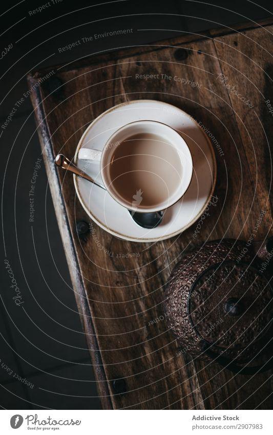 Cup of tea on table Tea Milk Table Teapot Fresh Saucer Spoon Drinking brewed Dark Room Cozy Hot Warmth Healthy Preparation Portion Breakfast Coffee ceramic