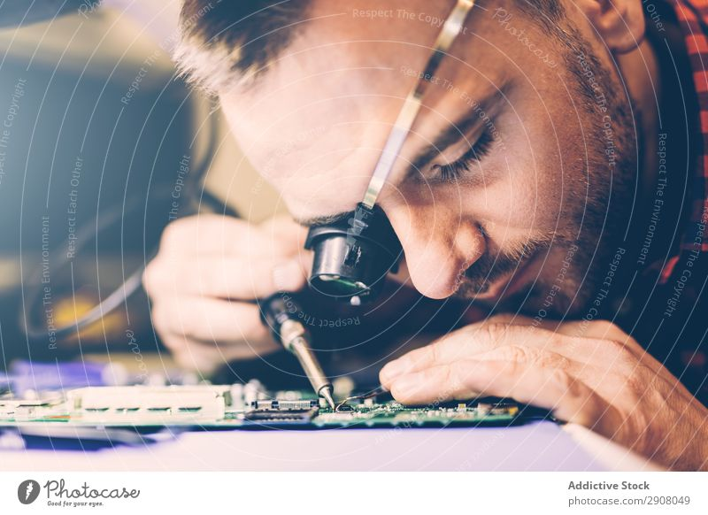 Man soldering motherboard at workplace Engineer Soldering Motherboard repairing magnifier Eyes Workplace Youth (Young adults) Guy Table workspace Technology