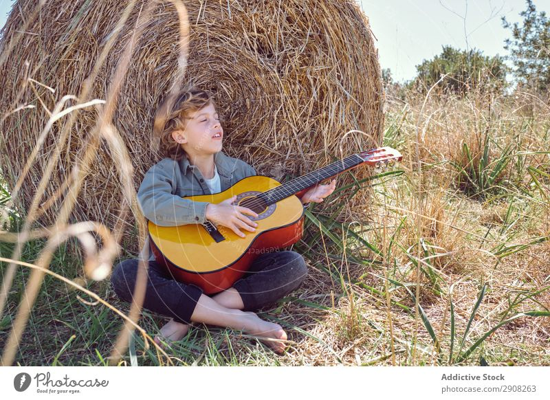 Boy playing guitar and singing near roll of hay Boy (child) Guitar Playing Music Field Hay Roll Closed eyes Landscape Child Grass Dry Song Acoustic instrument