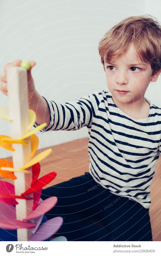 Boy playing with wooden construction pieces Action Blonde Boy (child) Build Child Infancy Creativity Cute Education To enjoy Joy Happy Home indoor Marble