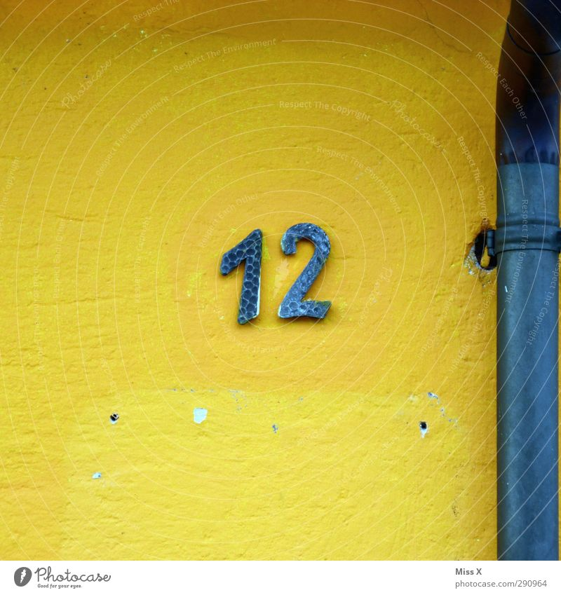 12 Sign Characters Signs and labeling Blue Yellow House (Residential Structure) Wall (building) Conduit Digits and numbers House number Colour photo
