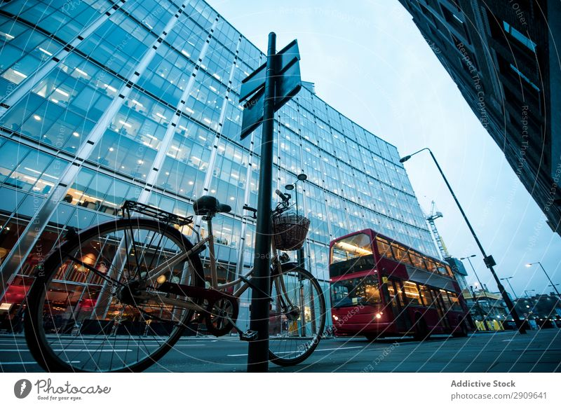 Bicycle and bus on city street double-decker Street City Bus Exterior London England Parked signpost Building Illuminate Evening Deserted Transport Vehicle Town
