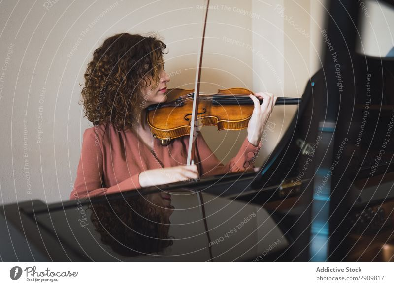 Woman sitting next to a piano playing a violin Fiddle Playing Music Violinist Orchestra instrument Classical Musician Hand Musical Human being String