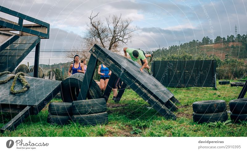 Participants in obstacle course climbing wall Lifestyle Sports Climbing Mountaineering Human being Woman Adults Man Group Meadow Jump Authentic Strong Green