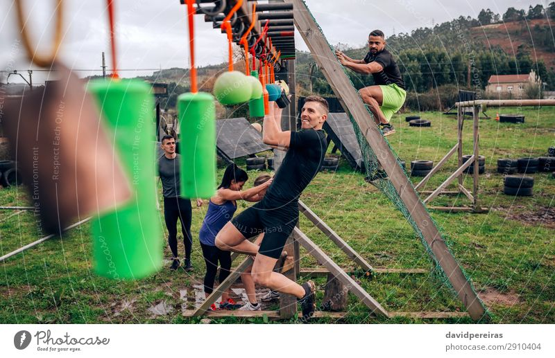 Participant obstacle course doing suspension Sports Human being Woman Adults Man Arm Group Observe Fitness Hang Authentic Strong Black Power Effort Competition