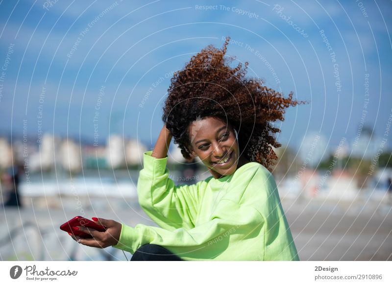 Side view of a young curly afro woman sitting on breakwater Lifestyle Style Beautiful Hair and hairstyles Ocean Music Telephone PDA Human being Feminine
