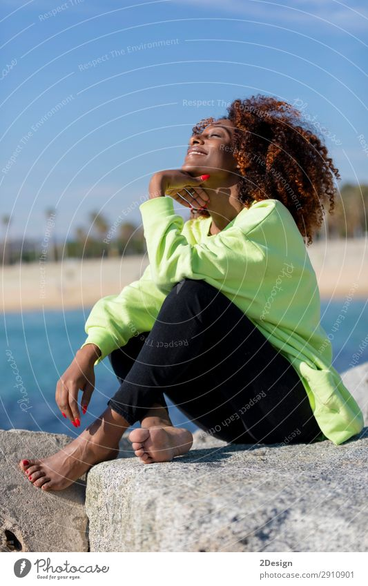 Side view of beautiful curly afro woman sitting on breakwater Woman Human being Youth (Young adults) Young woman Beautiful Hand Ocean Black 18 - 30 years Face