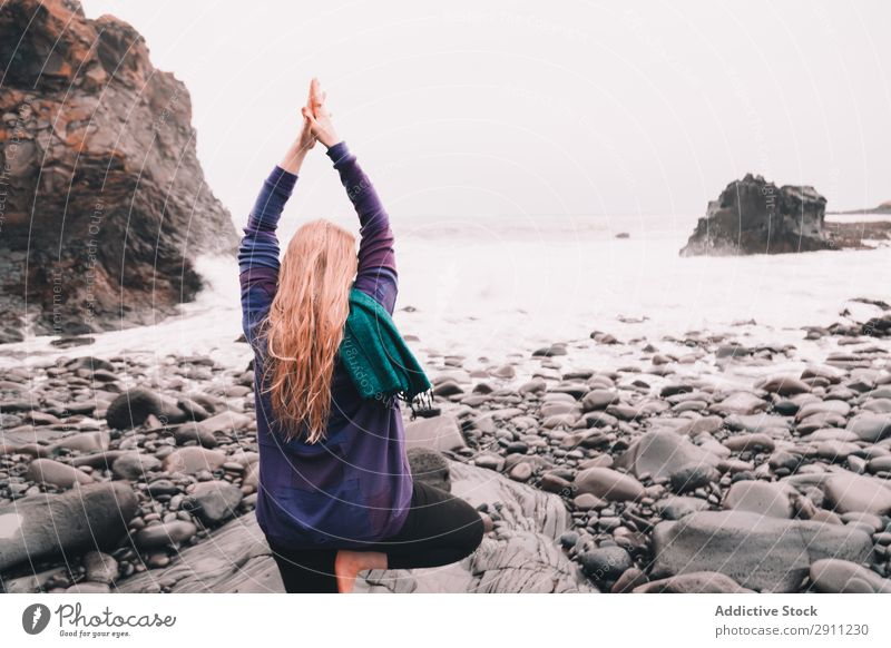 Woman on stones near sea coast Ocean Stone meditating upped hands Rock Water Hill Speed Splash Energy Youth (Young adults) Nature Yoga Concentrate Lifestyle