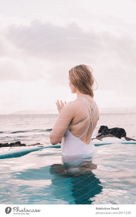 Woman sitting in pool near stones Swimming pool Stone Youth (Young adults) Resting Water Closed eyes Rock Sky Clouds Summer Body Relaxation Healthy Nature