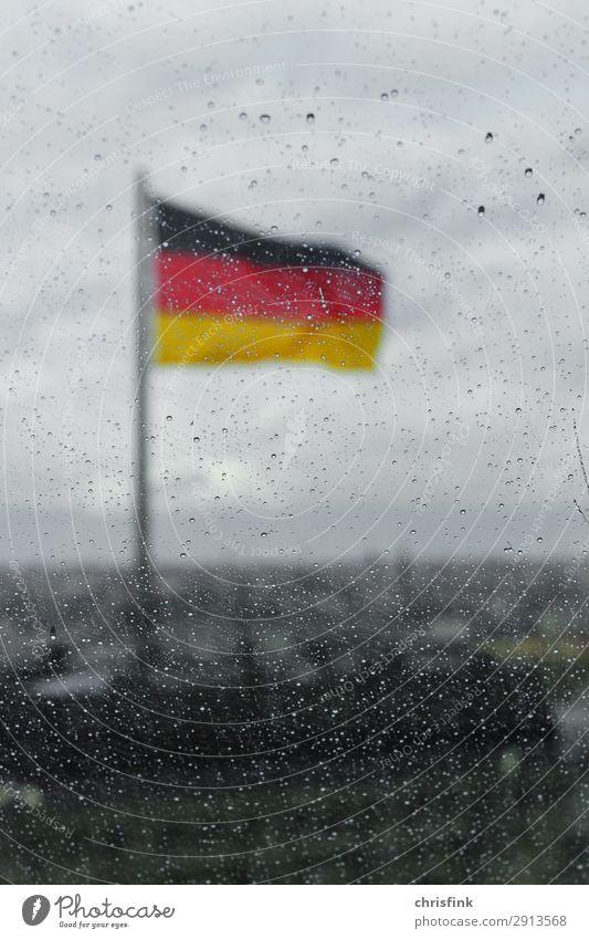 German flag behind drops on glass pane in Berlin Town House (Residential Structure) Building Roof Glass Sign Flag Cold Rain Blur Germany Colour photo Evening