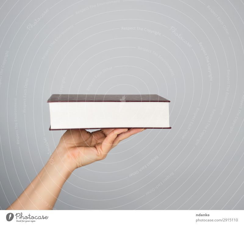 hand holds a closed book in hardcover Reading Human being Woman Adults Man Arm Hand Book Paper Brown Gray White background Blank Conceptual design education