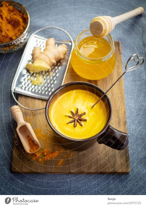 Golden milk with honey and ginger Food Dairy Products Herbs and spices Curcuma Honey Ginger Star aniseed Nutrition Beverage Hot drink Milk Cup Chopping board