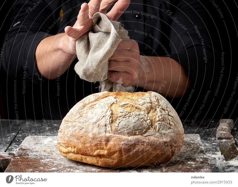 baked round bread on a board Dough Baked goods Bread Nutrition Knives Table Kitchen Cook Human being Hand Wood Make Dark Fresh Brown Black Tradition prepare