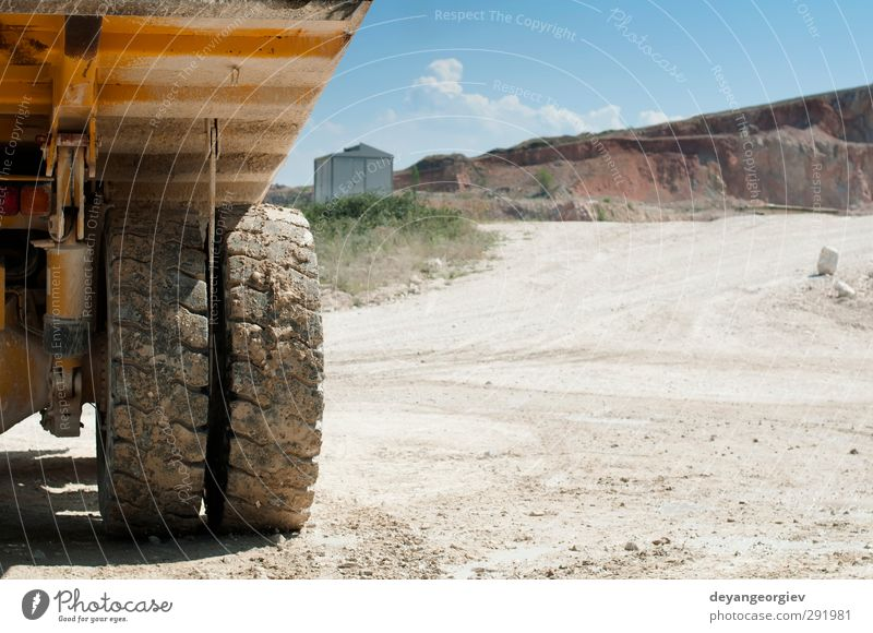 Truck in the quarry. Close up tire and trailer Sky Blue Yellow Sand Stone Rock Work and employment Transport Technology Ground Industry Strong Steel Vehicle